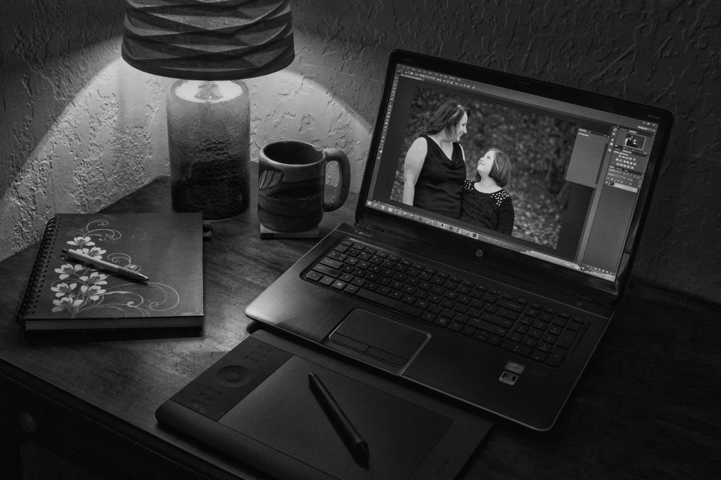 laptop open on desk with lamp, notebook, tea mug, tablet